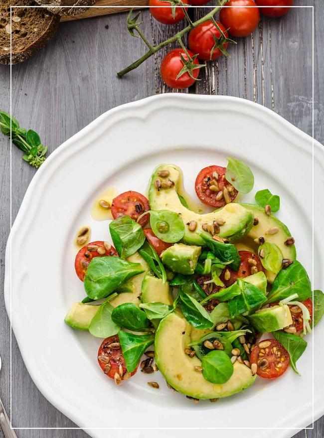 Avocado mit Tomate, Feldsalat und Pinienkernen