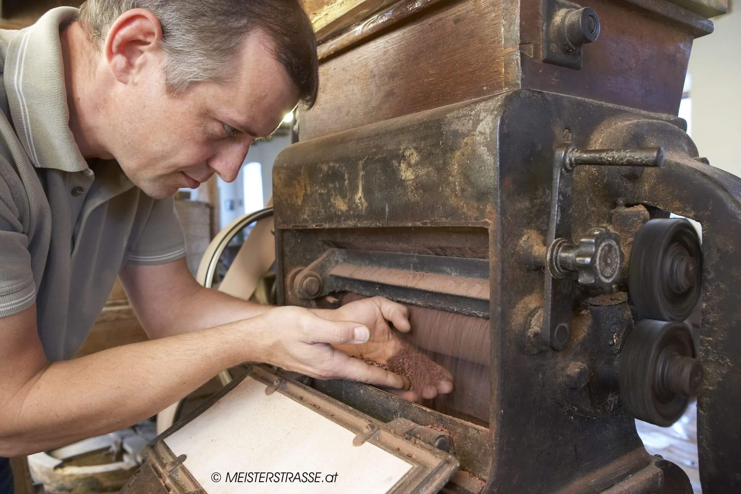 Thomas Hartlieb an einer alten Mahlmaschine